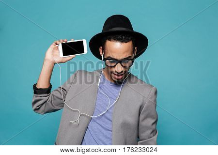 Portrait of a young afro american man in hat and eyeglasses showing mobile phone with blank screen over blue background