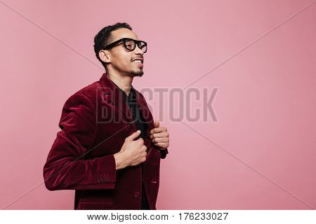 Portrait of a young smiling african man in jacket and eyeglasses standing and looking away isolated on the pink background