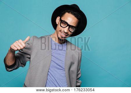 Portrait of a smiling stylish african man in eyeglasses showing thumbs up gesture over blue background