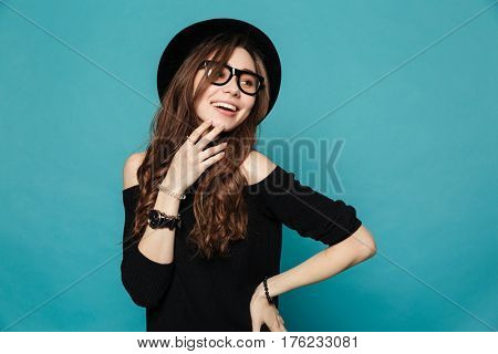 Portrait of a happy cute casual girl in hat and glasses looking away over blue background