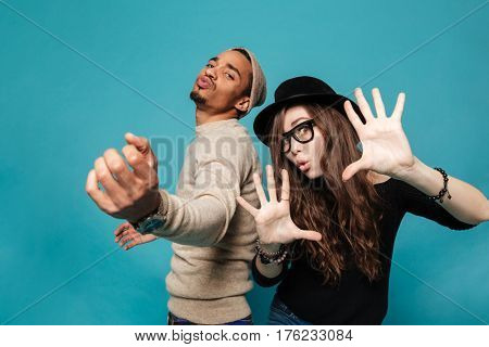 Portrait of a funny young modern couple dancing and having fun together over blue background