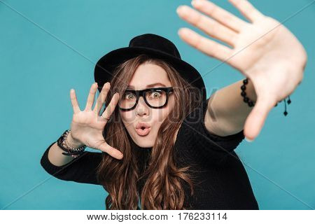 Close up portrait of a young pretty girl in hat dancing and making hand gestures isolated on a blue background