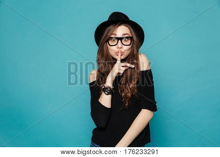 Portrait of a young pretty woman in hat showing silence gesture and looking at camera isolated on the blue background