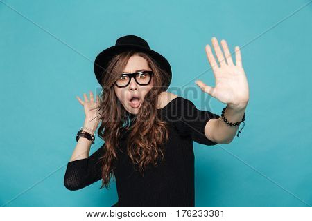 Portrait of casual surprised woman gesturing stop isolated on the blue background