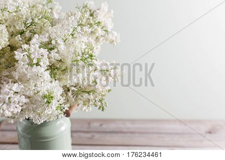 Lilac white Syringa flowers in vase. Spring background with white flowers in rustic Can on wooden table