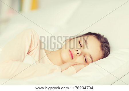 people, children, rest and comfort concept - girl sleeping in bed at home