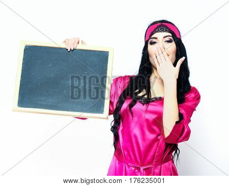 pretty cute sexy girl or beautiful woman with fashion makeup on surprised face and curly long hair in pink or fuchsia silk robe with bandage on head holding black board isolated on white background
