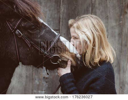 Portrait of a dark horse and woman, young blond woman kissing horse