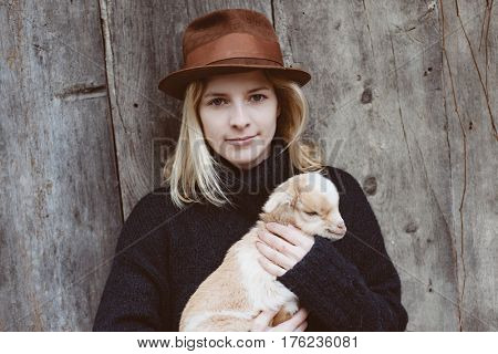 Cute baby goat in young adult woman hands