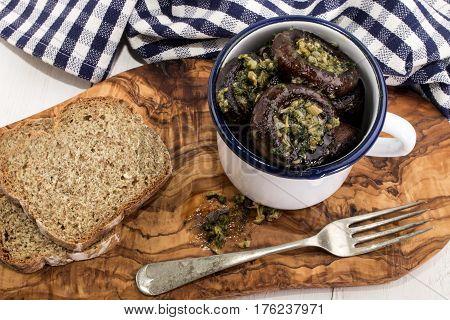 fried garlic and parsley filled chestnut mushroom in a white enamel cup with irish soda bread
