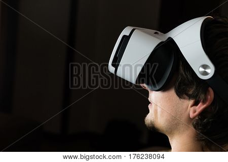 Person in virtual reality headset. Portrait of young man wearing vr glasses with dark background