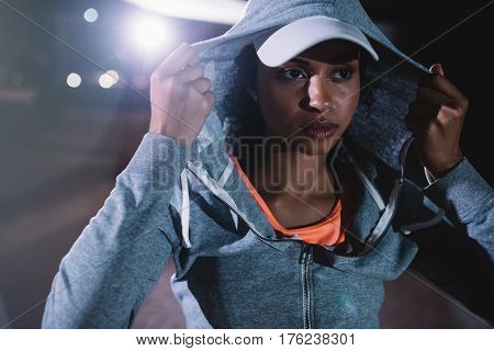 Portrait of urban runner standing on the street at night. Young woman in sportswear standing outdoors.