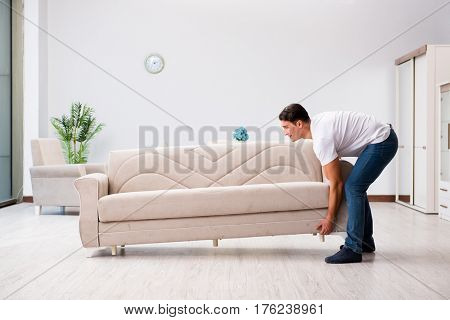 Young man moving furniture at home