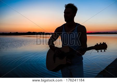 Silhouette of young handsome man playing guitar at seaside at sunrise. Outdoors.