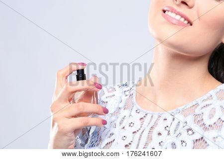 Beautiful young woman with bottle of perfume on light background, closeup
