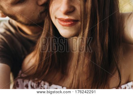 Stylish Man And Woman Hugging, Kissing And Smiling. Tender Romantic Moment In Summer Evening Light.