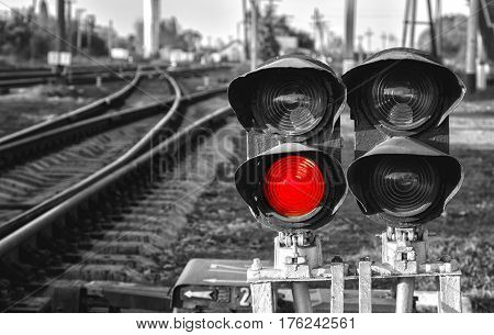 Black and white close up view of Traffic light shows red signal on railway. Red light