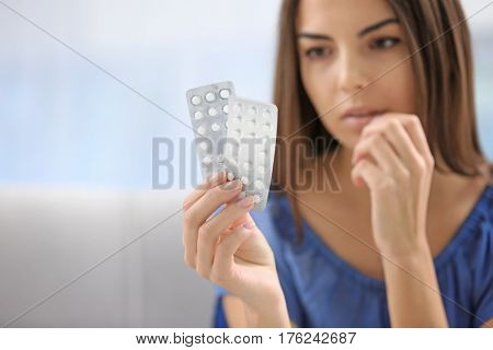 Young woman with pills at home, closeup. Gynecology concept