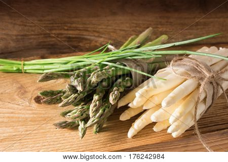 Bunch of fresh asparagus with chives on a rustic wooden table