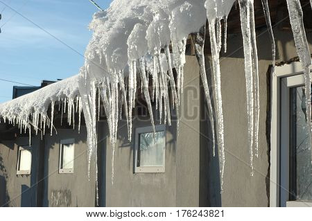 Icicles hang from the roof on a sunny frosty winter day.
