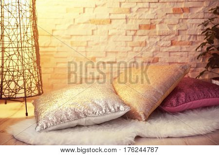 Three shiny decorative pillows on furry rug against brick wall background