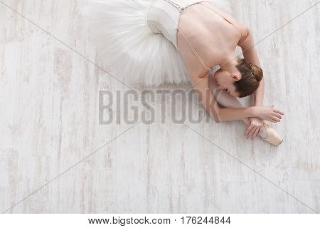 Beautiful graceful young ballerina in pointe shoes at white wooden floor background, top view from above with copy space. Ballet practice and stretching. Back of ballet dancer.