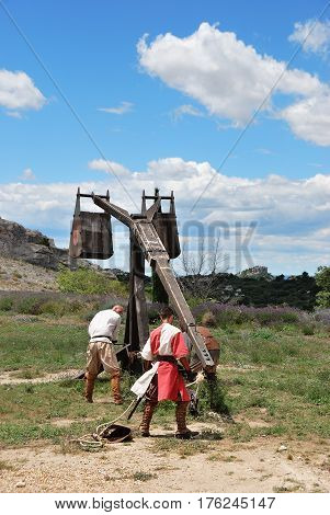 LES BAUX FRANCE - JUL 9 2014: Amateur historical reconstruction of medieval wars. Mens dressed as medieval warrior charge the catapult for fire. Les Baux castle