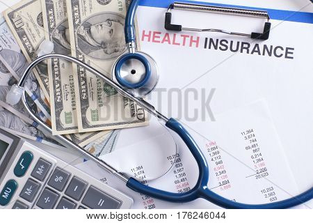 Health insurance concept. Calculator, stethoscope and banknotes on clipboard