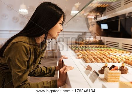 Image of cheerful asian young lady standing at the cafe. Looking at sweeties.