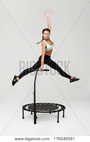 Young sporty woman in blue top and black pants jumping up on rebounder looking straight