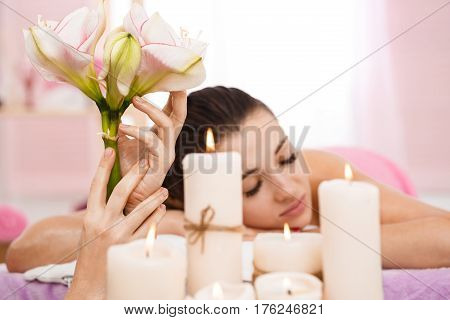 Woman relaxing at spa in bright room with lighted candles and tender flowers. Good vibes
