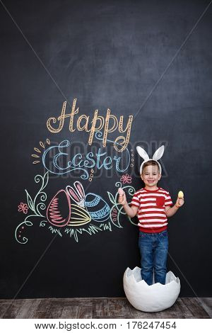 Laughing cute little boy wearing rabbit ears and holding two eggs while standing inside big cracked eggshell over chalk board with easter doodles background