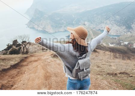 Girl wearing hat and sweater travel in mountains alone. Cold weather, calm scene. Backpacker walking outdoors in fall, back view over landscape. Wanderlust photo series.