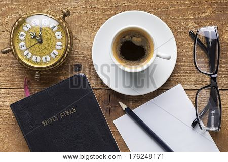 Holy Bible alarm clock glasses and coffee on wood table. Studying the Bible concept. Focus on the Bible.