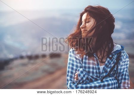 Girl travel in mountains alone. Spring weather, calm scene. Backpacker walking outdoors, view over landscape in sunlight. Wanderlust photo series.