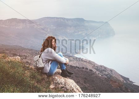 Girl travel in mountains alone. Spring weather, calm scene. Backpacker walking outdoors, back view over landscape. Wanderlust photo series.