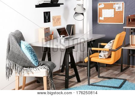 Workplace with a table and chairs in a teenage boy's room