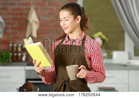 Woman in apron holding cookbook in kitchen