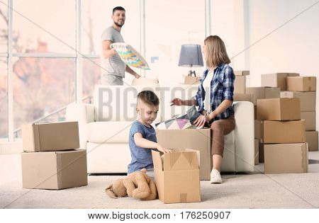 Happy family packing boxes in room. Moving concept