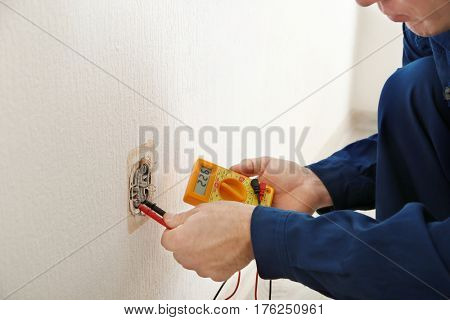Electrician measuring voltage of socket in new building, closeup