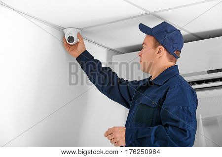 Electrician connecting CCTV camera in office