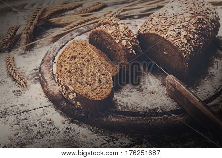 Bakery and grocery concept background. Fresh, healthy whole grain sliced bread loaf, sprinkled flour, wheat ears and knife cutting it on rustic table and wooden round desk, food closeup. Dark filtered