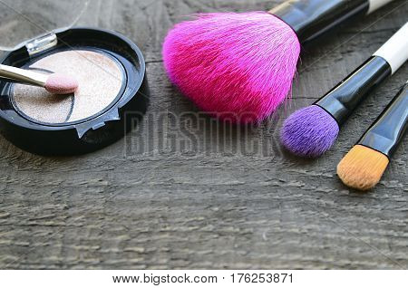 Makeup brushes and eye shadow on old wooden background with copy space.Various make-up products.Fashion cosmetic makeup or woman beauty accessories concept.Selective focus.