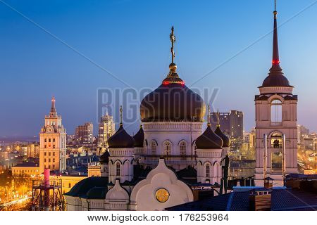 The Annunciation Cathedral (Orthodox Church ) in the center of Voronezh city, Russia, at background of South-East Railway Administration Building, after sunset