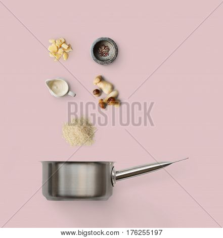 Cooking italian food, risotto with wild mushrooms, isolated on pink background. Rice, fungus, sauce, parmesan and other ingredients over saucepan