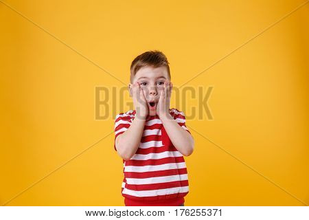 Surprised little kid with hands on his face isolated over orange background