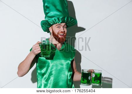 Happy bearded man in green costume which holding cups of green beer and looking at camera over gray background