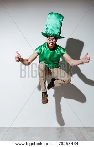 Full length of jumping happy man in green st.patriks costume which showing thumbs up, screaming and looking at camera. Isolated gray background