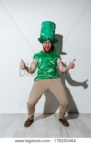 Full length of screaming man in green costume of st.patriks which showing thumbs up and looking at camera. Isolated gray background