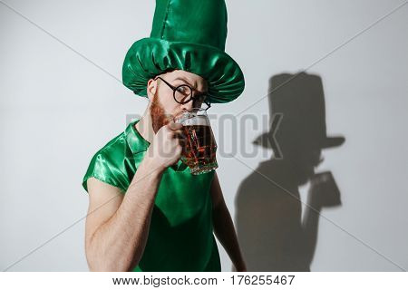 Serious man in st.patriks costume and eyeglasses which drinking beer and looking at camera over gray background
